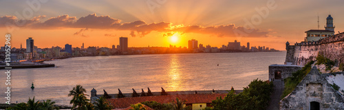 Sunset in Havana with the sun setting over the seaside buildings including a view of El Morro lighthouse