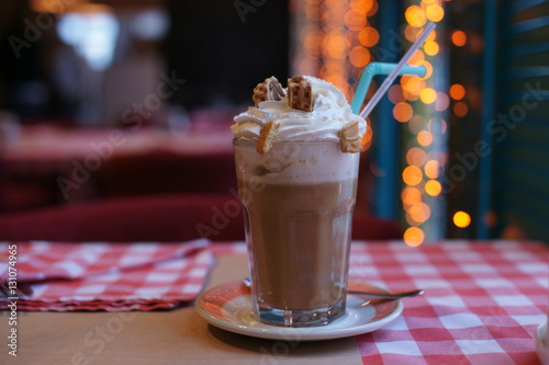 Foto op Plexiglas Milkshake Big cup of coffee with cream and wafers on a table in a restaurant