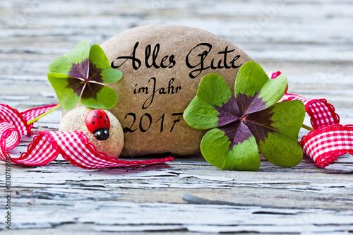 Fotografia  vierblättrige Kleeblätter, Marienkäfer und Stein auf Holz, Alles Gute im Jahr 20
