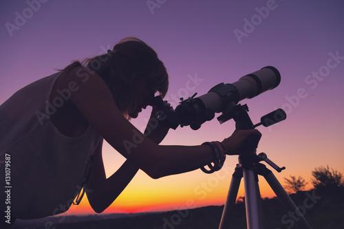 Fototapeta Girl looking at the stars through a telescope. obraz