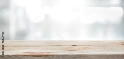 .Wood table top on blur glass window wall building background.
