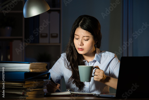 Fotografie, Obraz  asian business woman drink coffee working overtime late night