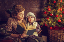 Mother Reads To His Son The Book Near A Christmas Tree.