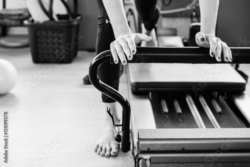 Photo  Pilates reformer exercise's detail in black and white.