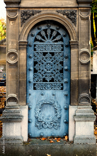 Old blue iron door on an exterior tomb / crypt wall. Round arch and chiseled & Old blue iron door on an exterior tomb / crypt wall. Round arch and ...