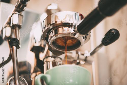 Fotografija Fresh morning espresso coffee pouring through the bottomless portafilter