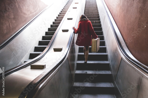 woman go up the subway stairs keeping luggage