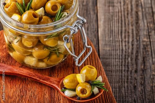 Foto op Canvas Olijfboom Fresh olives with rosemary, garlic, lemon.