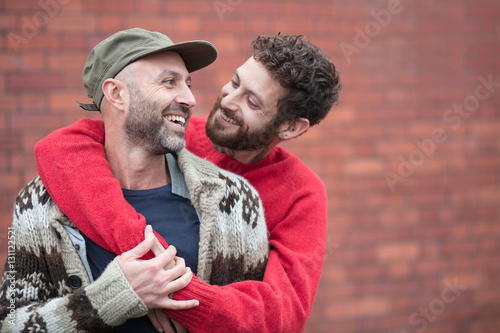 Fotografie, Obraz  Gay couple cuddling and laughing in front of brick wall