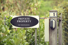 Private Property Notice On Gate Saying No Trespassing On Blurred Background. Selective Focus