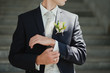 canvas print picture - Groom buttons his shirt at the wedding