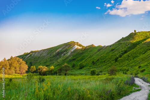 Fotobehang Heuvel Green chalk hills under blue sky. The multilayered archaeological monument - Krapivinskaya settlement, Belgorod region, Russia. Summer landscape.