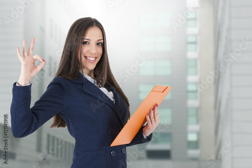 Fotografía  women's business attractive with the dossier and the sign of approval and okay s