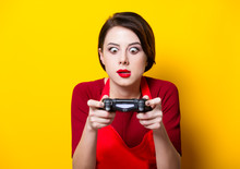 WROCLAW, POLAND - 20 December 2017: Young Housewife With PlayStation 4 Joystick On Yellow Background, Wroclaw, Poland