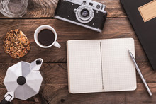 Vintage Hipster Wooden Desktop With Notebook Opened, Vintage Camera, Cup Of Coffee And Coffee Maker