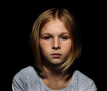 Portrait Of Sad Little Girl On Black Background