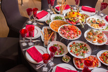 Round Table Decorated With Red Wine Glasses, A Black Tablecloth And Italian Dishes