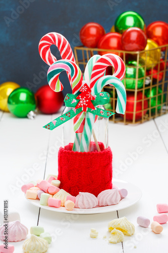 set of christmas sweets colored candy cane and pastel marshmallows on a light wooden background