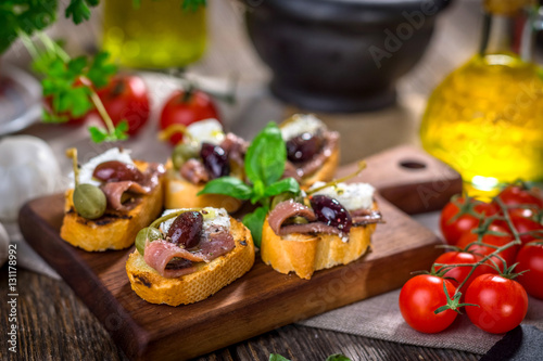 Tasty bruschetta with anchovy,  feta, caper, olive oil ... Wallpaper Mural