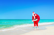 Santa Claus walks with large Christmas gifts sack at ocean beach