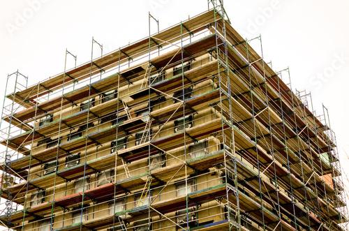 Fototapeta bare brickwork of a building with scaffold obraz na płótnie
