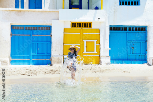 Greece, Milos, Firopotamos Beach, Womsn running into sea, splashing water