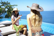 Two women enjoying cocktails at ocean front infinity swimming pool