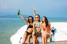 Three Beautiful Cheerful Wet Hipster Girls On The Beach, Sitting On A Speedboat, Drink Beer, Merry Company, Best Friends, Sexy Bikinis, Sunglasses, Crazy Emotions, Grimace, Scream, Party Friends