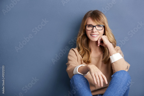 Fényképezés  Shot of a mature woman with pretty face sitting by the wall while wearing casual clothing and smiling