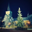 Beautiful night winter photo Christmas tree with church and snow.