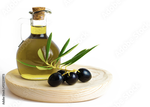 Olive Oil  with olives on a wooden board.