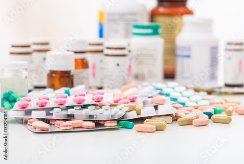 Fotografia  Stack of pills and containers on white background