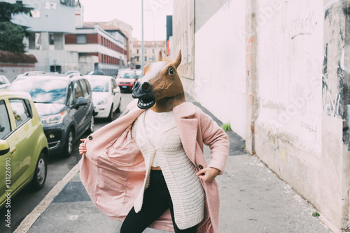 Canvas Woman wearing horse mask dancing outdoor in the city - strange, absurd, carnival