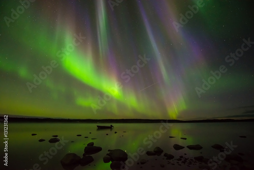 Photo  Colors of Northern Lights - Multi-colored aurora borealis hovering over a rocky lake