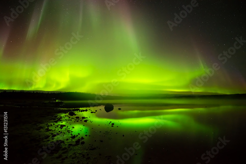 Photo  Rolling Lights - Layers of bright rolling northern lights reflecting in a rocky lake