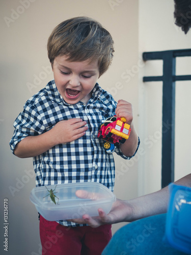 24cb0e273 Cute child in a plaid shirt and red pants scared beetle, which sits in a