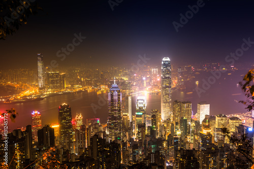Photo Stands Kuala Lumpur Aerial view of Victoria Harbour skyline by night from Lugard Road Lookout at Victoria Peak, the highest mountain in Hong Kong Island. On backgrond, the landmark skyscrapers with their lights and neon.