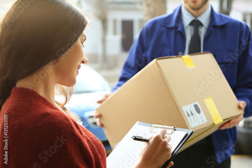 Fotografie, Obraz  Young woman signing documents after receiving parcel from courier, closeup