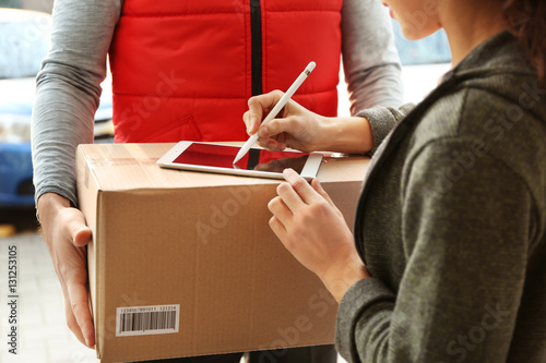 Young woman appending signature after receiving parcel from courier, closeup Canvas Print