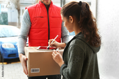 Photo Young woman appending signature after receiving parcel from courier