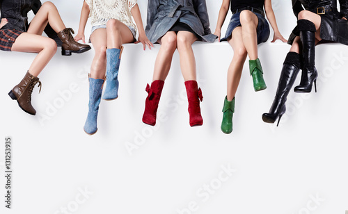 Fototapeta Many colorful boots women sitting together on the white bench. Woman shoes collection.  obraz