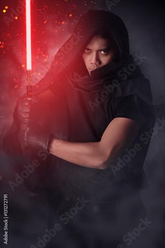 Photographie  Guerrier tenant un sabre laser rouge