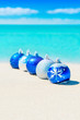 Christmas tree blue and silver balls decorations on beach sand vertical background