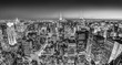New York City. Manhattan downtown skyline with illuminated Empire State Building and skyscrapers at dusk. Black and white image. Panoramic composition.