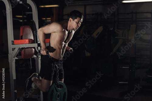Muscular bodybuilder working out in gym doing exercises on parallel bars. Athletic male naked torso.