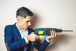 man businessman holds in hand a power drill