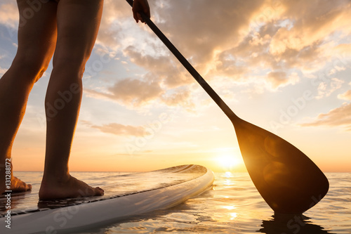 Fotomural  Stand up paddle boarding on quiet sea, legs close-up, sunset