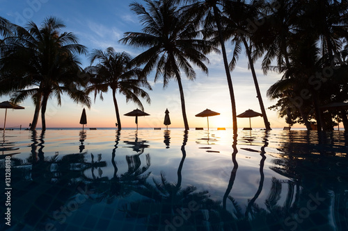 Wall Murals Bali Palm trees and reflection in swimming pool, beach hotel, sunset