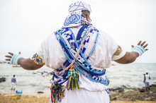 A Brazilian Candomble Priest Performs A Blessing At The Festival Of Yemanja In Traditional Blue And White Robes With Colorful Beads On The Beach At Rio Vermelho In Salvador, Bahia, Brazil