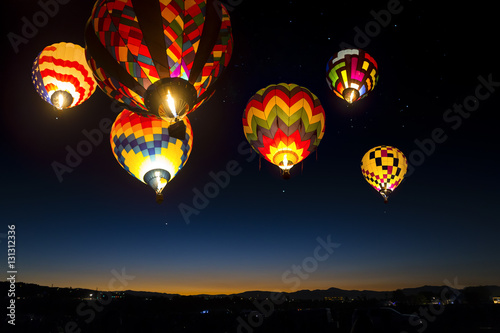 Colorful hot air balloons at dawn lit up in the sky.